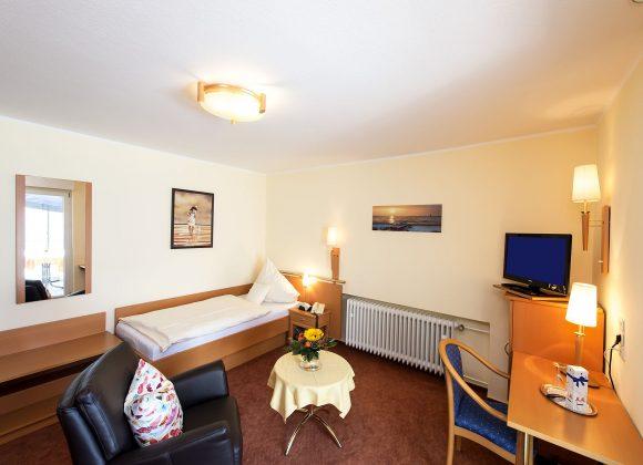 Einzelzimmer mit Sessel und TV
